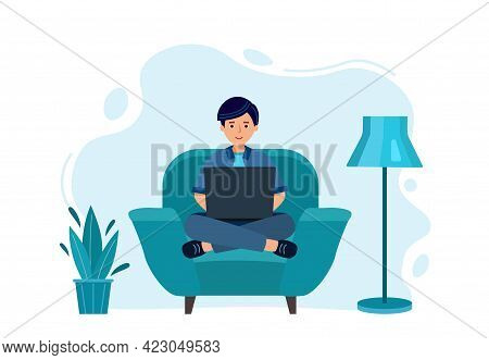 Man Work On Laptop. Works At Home, Sits On Blue Chair. Studying Distantly