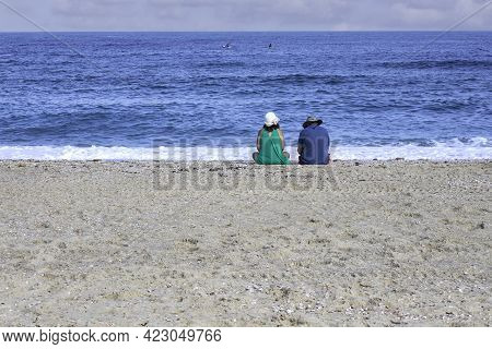 Couple Man And Woman Sitting Next To The Water On The Sandy Beach On The Mediterranean Coast