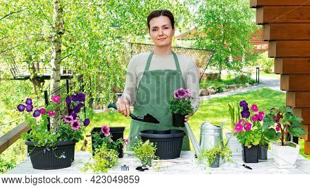 Portrait Of A Cute Woman Gardener Who Transplants Flowers Into Flower Pots To Decorate The Garden An