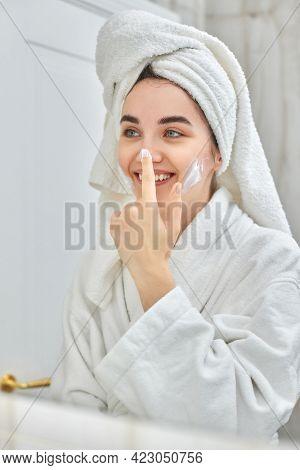 Woman In White Bathrobes Applying Apply Facial Cream