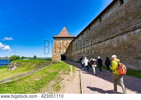 A Group Of Tourists Walks Along A Brick Fortress Wall With A Tower. Fortress Oreshek On A Sunny Summ