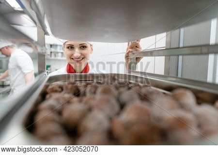 Women cook getting frozen meatball out of storage on a tray