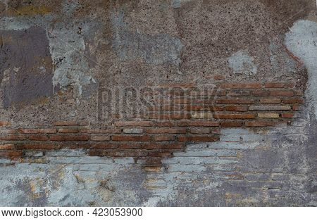 Old Wall Background. Ancient Brickwork With Narrow Red Bricks, Partly Damaged And Colored. The Photo