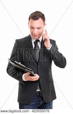 Portrait Of A Young Fashionable Businessman, Looking At A Clipboard And Talking On A Mobile Phone, L