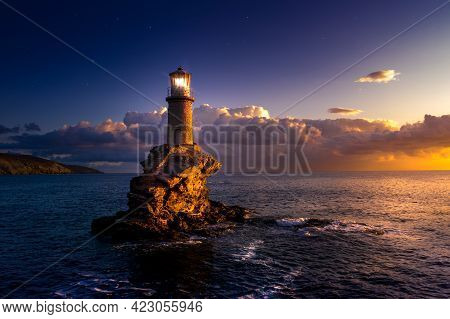 The Beautiful Lighthouse Tourlitis Of Chora At Night. Andros Island, Cyclades, Greece