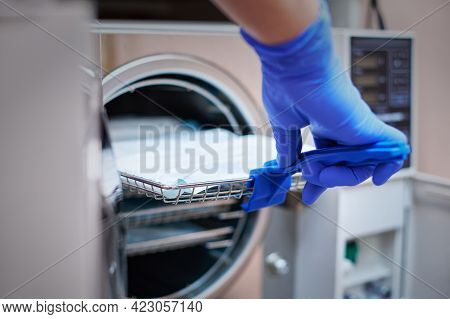 Dentist In Blue Latex Gloves Is Taking A Sealed Dental Stainless Steel Instrument From An Autoclave