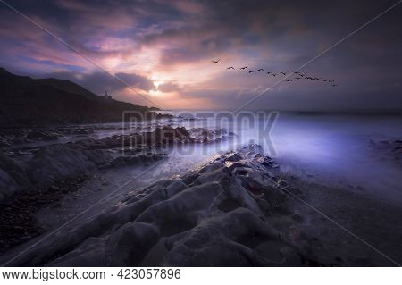 Birds Fly At Daybreak Over The Rock Pools At Bracelet Bay On The Gower Peninsula In Swansea, South W