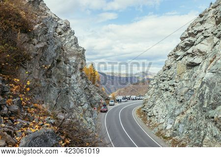 Several Cars Parked By Mountain Highway Between Rocks In Autumn Colors. Cars On Mountain Pass And Au