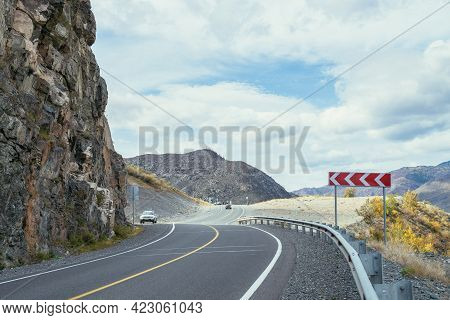 Several Car On Mountain Highway Along Rocks In Sunshine In Autumn Colors. Colorful Landscape With Mo