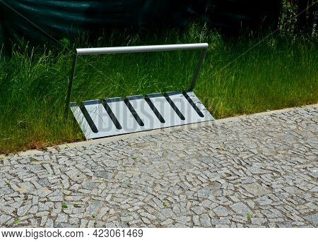 Bike Wheel Racks Of Gray Sheet Metal Tubes In The Shape Of A Rectangle On The Lawn, Paving Of Granit