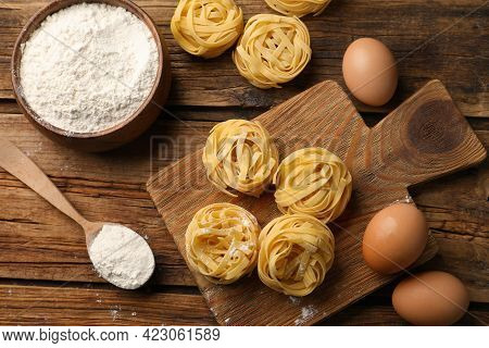 Uncooked Homemade Pasta And Ingredients On Wooden Table, Flat Lay