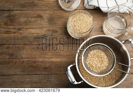 Rice And Kitchenware On Wooden Table, Flat Lay. Space Or Text