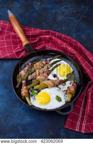 A Dish Of Asparagus, Bacon And Eggs In A Cast-iron Skillet On A Dark Background. A Nutritious Breakf