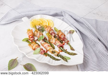 A Dish Of Asparagus And Bacon On A White Plate. Baked Green Asparagus Wrapped In Bacon. Healthy Food