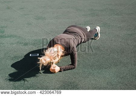 Woman Doing Workout Outdoors. Sportswoman In A Tight Tracksuit Doing Plank Exercise For A While On A