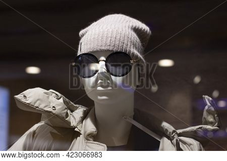 The Head Of A Mannequin In A Hat And Sunglasses, Glare From Glass And Lamps. Mannequin In A Knitted