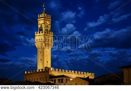 Florence, Tuscany, Italy. Tower of Palazzo Vecchio at night with clouds on the blue dramatic sky after sunset. Evening illumination on the ancient walls.