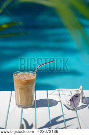 Ice Coffee Cyprus Frappe Fredo Against Blue Clear Water Of The Swimming Pool, On White Table, With S