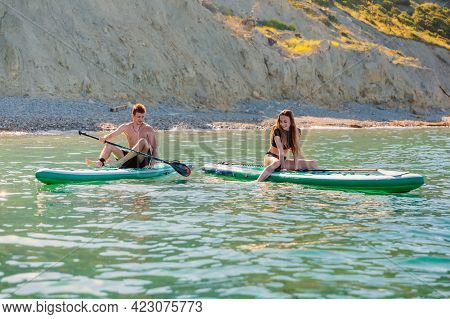 May 28, 2021. Anapa, Russia. Couple On Stand Up Paddle Board At Blue Sea. People Vacation On Red Pad
