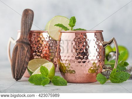Moscow Mule Cocktail In A Copper Mug With Lime And Mint And Wooden Squeezer On Light Kitchen Table B