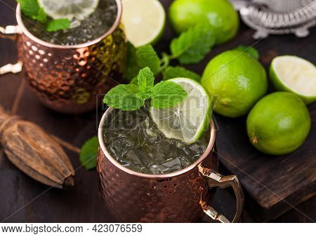 Moscow Mule Cocktail In A Copper Mug With Lime And Mint And Wooden Squeezer On Dark Wooden Table Bac