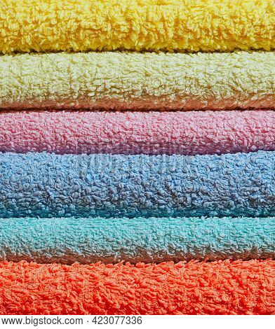 Terry cloth towels pile washed stack close up. Colorful clothes macro concept