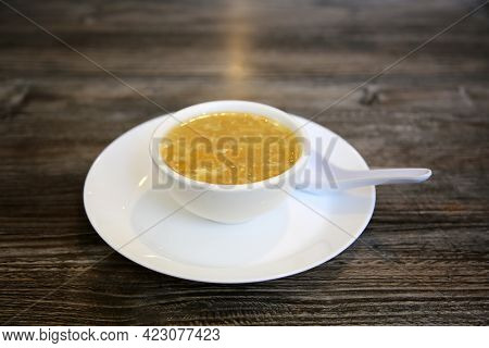 Egg drop soup made of beaten eggs drizzled in homemade chicken broth with green onions. egg drop soup. egg flower soup. Chinese food. Soup in a Chinese restaurant.