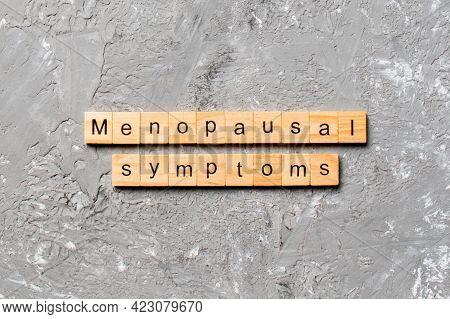 Menopausal Symptoms Word Written On Wood Block. Menopausal Symptoms Text On Cement Table For Your De