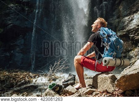 Man With Backpack Dressed In Active Trekking Clothes Drinking The Water From Touristic Flask Sitting