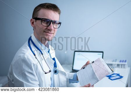 Cardiologist Reading An Ecg Print-out. Doctor Analyzing Electrocardiogram. Practitioner Examine Pati