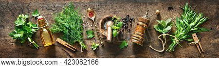 Panoramic background with bunches of fresh garden herbs, spices and kitchen utensils on rustic wooden table