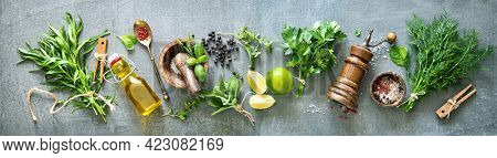 Panoramic background with bunches of fresh garden herbs, spices and kitchen utensils on rustic stone table