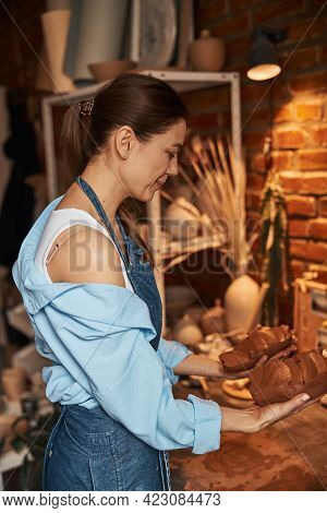 Charming Elegant Female Artisan Looking To The Earthenware Tool In Arms Above The Wooden Table In Ar