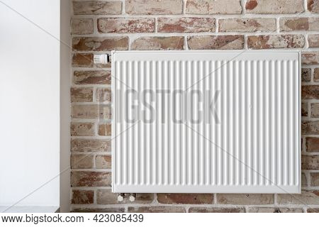 Close Up Shot Of Central Heating System Radiator With Thermostat On Brick Wall In Loft Style Interio