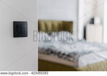 Selective Focus On Black Matt Electric Light Switch On White Wall With Big Comfy Bed In Blurred Back