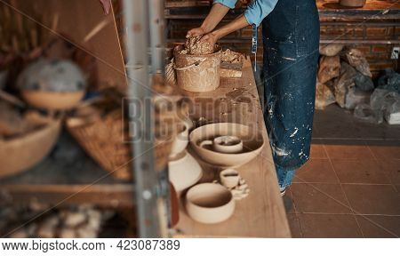 Beautiful Young Lady In Apron Working With Light Brown Earthenware Materials In Pottery Workshop