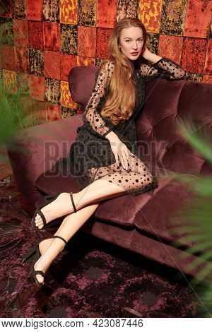 Full length portrait of a beautiful young woman in black evening dress sitting on a velvet sofa in luxury apartments. Beauty, fashion. Glamorous lifestyle. Modern interior, furniture.