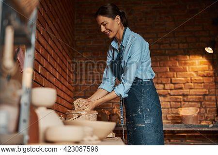 Beautiful Elegant Female Artisan Wearing Apron Working With Fresh Wet Earthenware Materials In Art S
