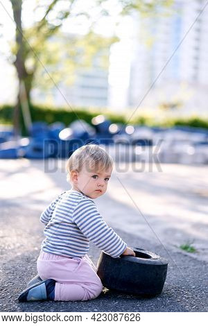 Child Sits With His Head Turned And Touches The Rim Of The Car In The Parking Lot
