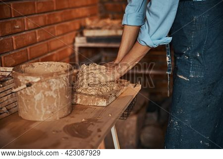 Unrecognized Craftswoman In Apron Working With Earthenware Materials In Art Studio