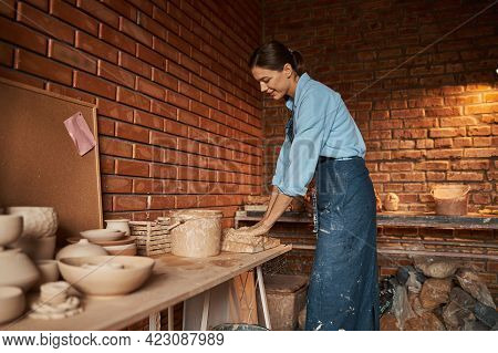 Young Caucasian Craftswoman Hanging Out In Art Studio While Squeezing Earthenware Materials In Art S