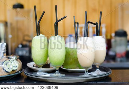 Kiwifruit And Almond Cream Juice In Glass Over Blur Fresh Coconut Juice In Tray Ready To Serve At Lo