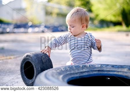 Kid Holds The Rim Of The Car In The Parking Lot