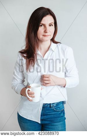 Beautiful Woman In A White Shirt Holding A White Ceramic Cup On A White Background. Woman Drinking W