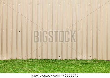 a metal sheet wall on a green grass poster