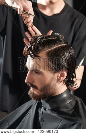 Good looking young man visiting hairstylist in barbershop.