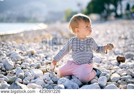 Kid Sits On His Knees With His Head Turned On A Pebble Beach And Holds A Pebble In His Hand