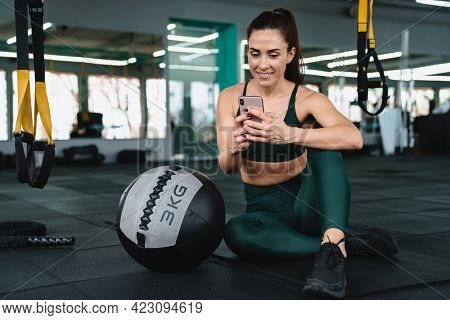 White sportswoman using cellphone while working out with medicine ball in gym