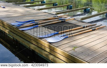 Classic Wooden Boat Oars. Plastic Boat Paddles Lie On A Wooden Pier, Boat Rental In The Park