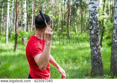A Man Throws A Knife At A Target In The Summer Forest, Back View. Throwing A Knife
